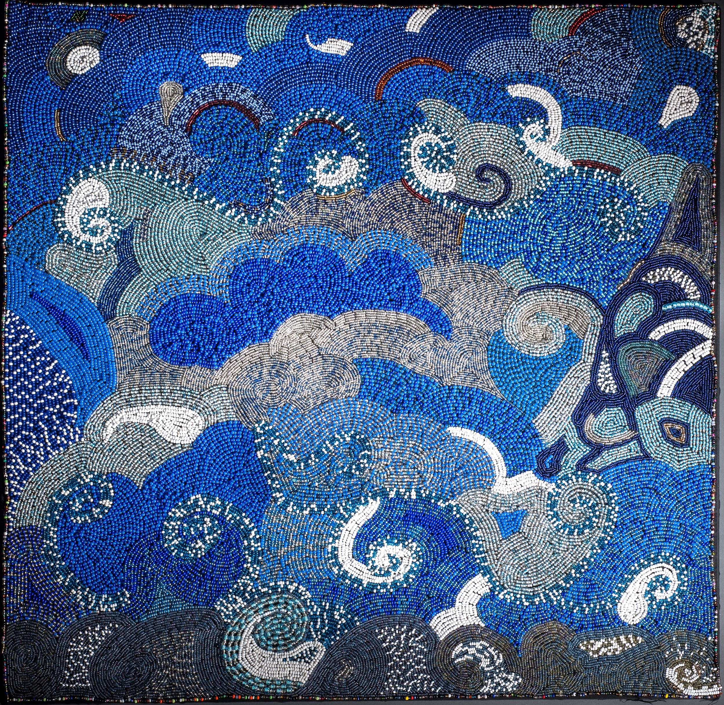 An image of radiating blue and grey clouds made out of glass beads sewn onto fabric