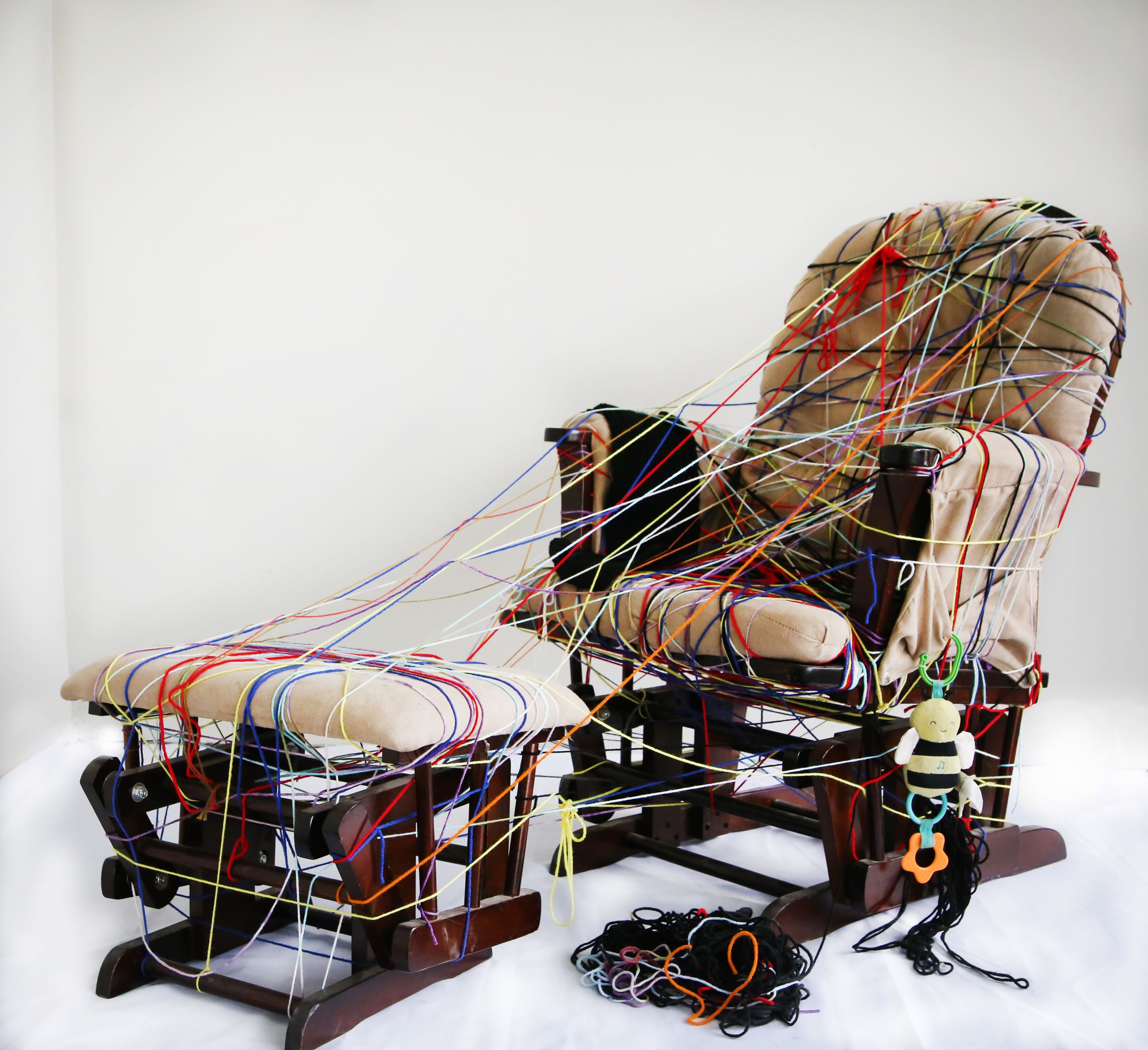 A lounging chair and ottoman covered in strings and children's toys.